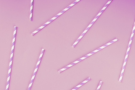 Purple paper straws on lillac color background. Pattern