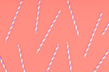 Purple paper straws on pink coral color background. Pattern