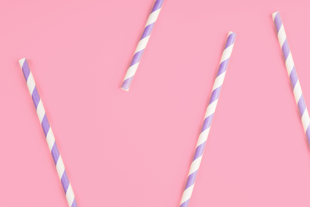 Purple paper straws on pink color background. Pattern