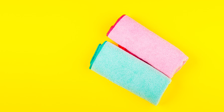 Colorful microfiber cloths on bright yellow background. Cleaning concept Фото со стока