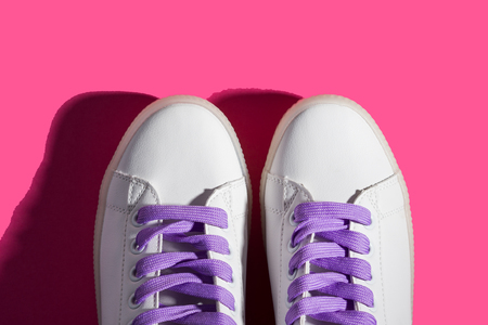 White sneakers with purple laces on pink background. Shadow. Modern minimal fashion art trendy bold color flat lay backdrop
