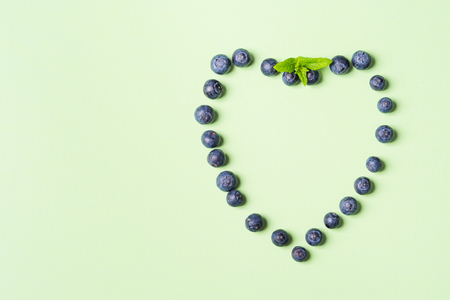 Fresh blueberries in shape of heart frame on pastel green background. Healthy breakfast concept Imagens - 122749200