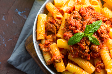 Delicious rigatoni pasta with italian tomato meat ragu sauce served in a pan on dark brown background. Traditional pasta dish concept. Home made lunch Stock Photo