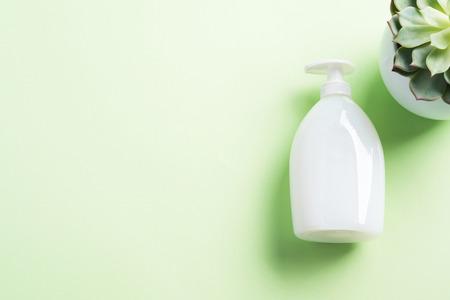 Bouteille de savon crème naturelle blanche sur fond vert pastel avec plante succulente. Produit de beauté générique.