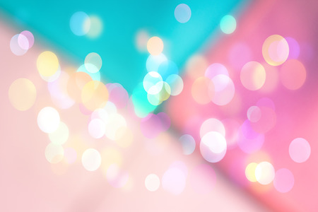 Abstract geometrical blurred background with sparkling light bokeh. Festive pink and turquoise backdrop