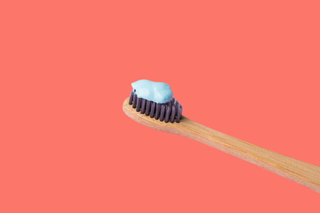Bamboo toothbrush with blue toothpaste isolated on coral background. Personal dental hygiene concept. Zero waste