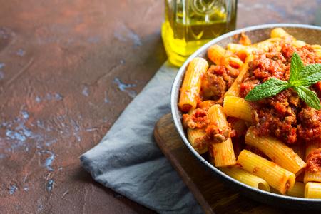 Deliziosi rigatoni con salsa di ragù di carne di pomodoro italiana servita in padella su sfondo marrone scuro. Concetto di piatto di pasta tradizionale. Pranzo fatto in casa