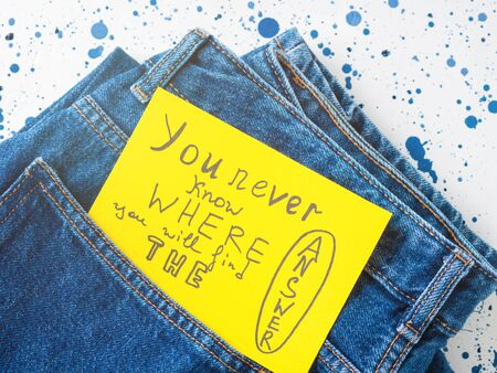 Jeans pocket with inspirational quote card on yellow background. You never know where you will find the answer. Self motivation.