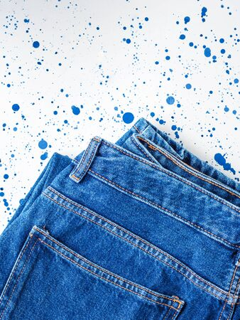Pair of denim jeans on white and blue background. Texture. Flat lay