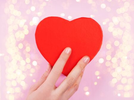 Womans hand holding red heart gift box on pink backdrop with sparkling festive lights Stock Photo
