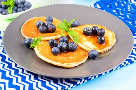 Pancakes served with fresh blueberries on gray plate over geometrical background. Healthy home made breakfast concept