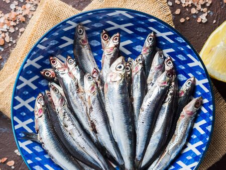 Blue fish. Fresh anchovies in a dish with pink salt and lemon on dark background. Healthy protein meal. Local seafood, Italy