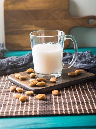 Vegan plant almond milk in a glass mug on wooden board. Фото со стока