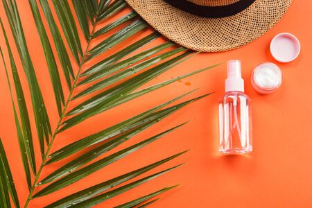 Sun protection concept flat lay with fern, hat, spray bottle and cream. Orange coral background.