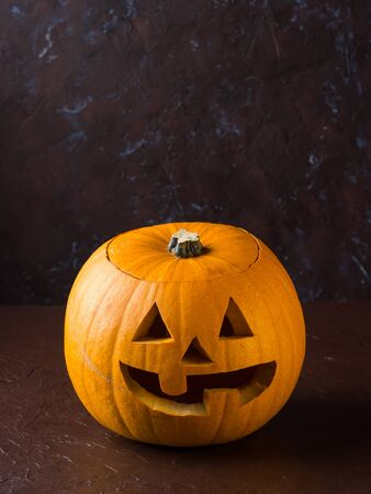 Halloween carved squash on dark brown background