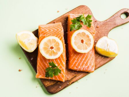 Salmon fillet on wooden board with lemon slices, parsley and pink salt. Pastel green background. Healthy fish meal to be cooked. Protein source.