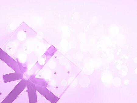 Gift box with purple ribbon bow with magic festive bokeh lights on abstract background. Copy space flat lay