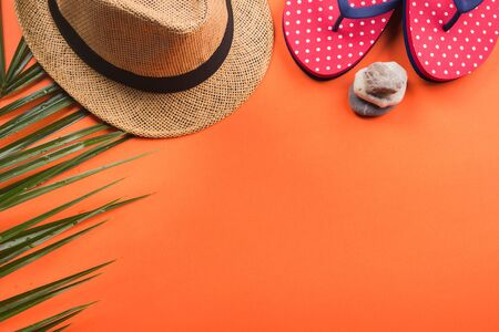 Vacation on the beach. Flat lay on orange coral background. Fern, hat, flip flops, stones. Фото со стока