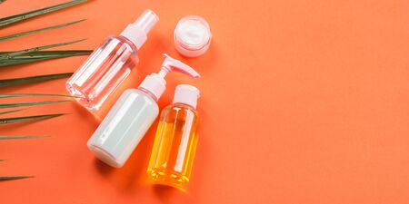 Generic beauty products on orange coral background. Summer travel kit or sun protection concept.