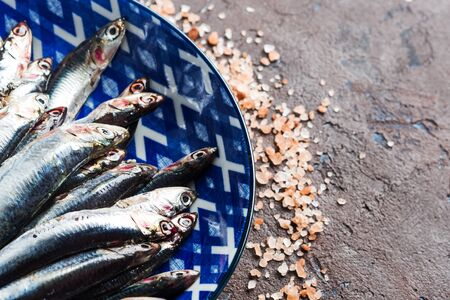 Blue fish. Fresh anchovies in a dish with pink salt on dark brown background. Healthy protein meal. Local seafood, Italy