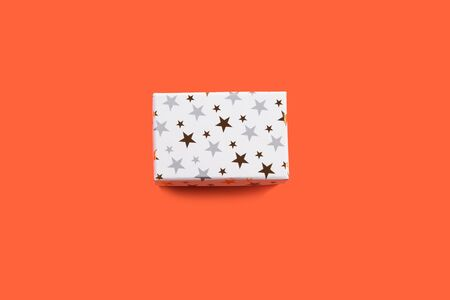 White gift box with golden stars on orange coral background. Giving presents concept.
