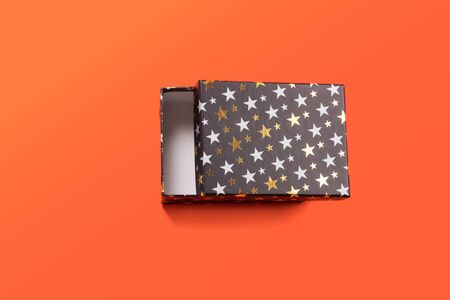Black half open gift box with golden stars on orange coral background. Giving presents concept.