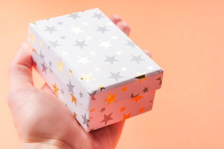 White gift box with golden stars in womans hand on orange coral background. Giving presents concept.