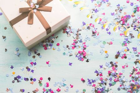 Pink gift with ribbon on colorful confetti and party streamers background. Copy space Stock Photo