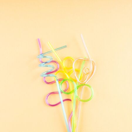 Colorful funny shape party cocktail straws on orange. Flat lay with copy space