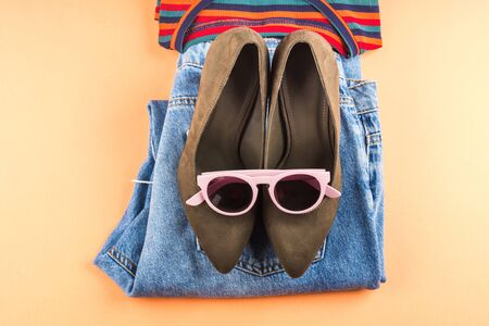 Fashion flat lay with folded jeans, green suede pumps and pink sunglasses on orange background Standard-Bild
