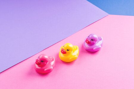 Colorful funny toy rubber ducks on color geometry backdrop