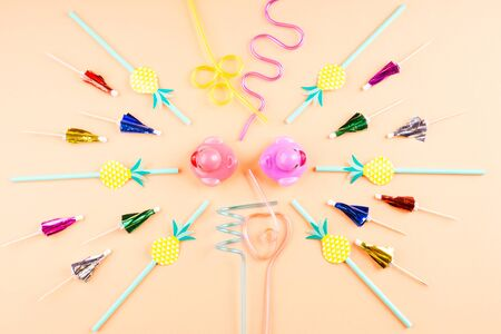 Funny party circle composition with paper straws, cocktail umbrellas and toy rubber ducks. Flat lay on orange pink background.