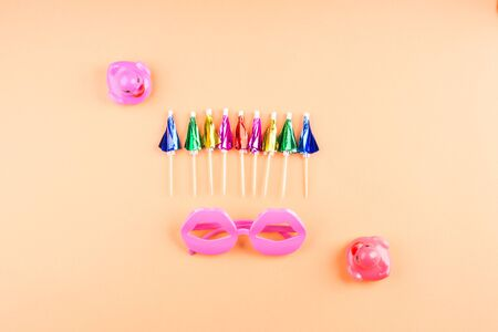 Rainbow shiny cocktail neon umbrellas, rubber ducks and funny glasses. Summer funky flat lay on orange pink background.