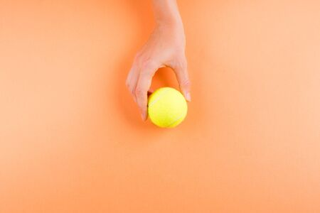 Tennis ball on abstract orange background in womans hands