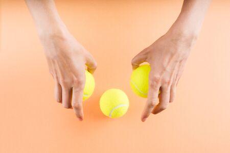 Three tennis balls on orange in womans hands