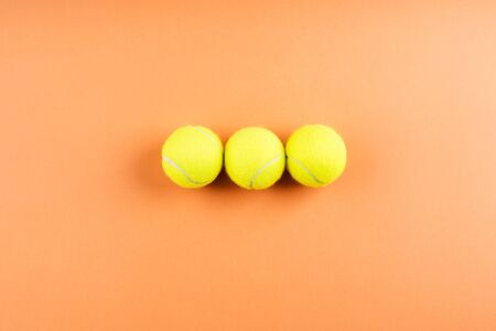 Three Tennis balls on orange abstract background. Competition concept