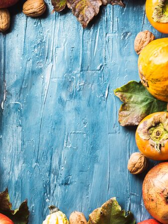 Autumn fruit thanksgiving background with persimmons, pomegranate, apples, nuts, squash on blue textured backdrop with fall leaves.