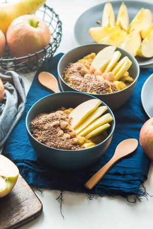 Turmeric amaranth porridge served with apples, flax seeds and almonds. Healthy plant based vegan breakfast.