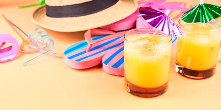 Vacation on the beach concept with colorful summer cocktails and beach accessories - hat, flip flops, sun glasses