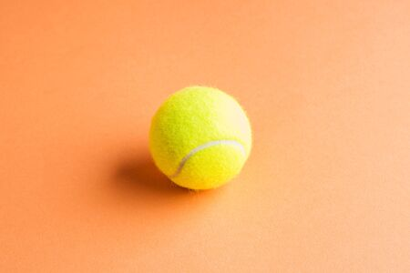Tennis ball on orange abstract background. Game concept