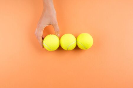Three tennis balls on orange. Womans hand reaching for one of the balls.