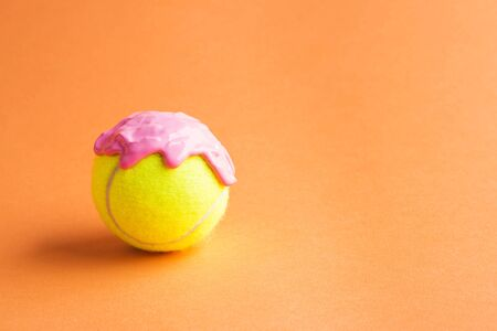 Tennis ball with pink paint as ice cream scoop on orange. Abstract art concept 写真素材