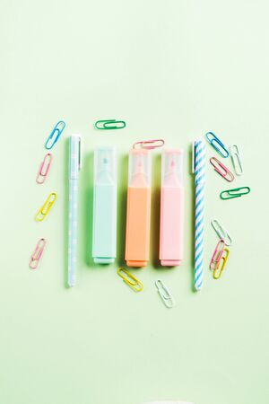 Pastel green back to school flat lay with colorful stationery - highlighters and clips. Blogging, writing concept 版權商用圖片