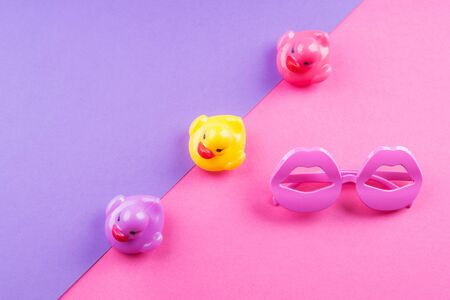 Colorful funky summer flat lay with funny items - rubber ducks, lip shape glasses. Pink and purple duotone background.