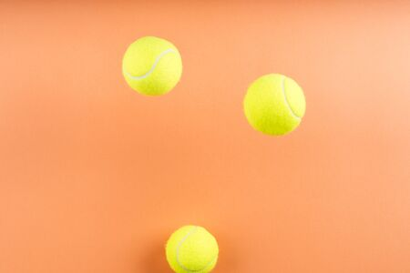 Tennis balls bouncing on orange abstract background. Competition concept Imagens
