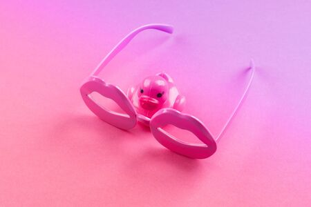 Pink funky rubber duck wearing lip shape glasses on neon monochrome. Pop art item composition. 版權商用圖片