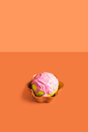 Tennis ball with pink paint as ice cream scoop in waffle cup on orange. Abstract art concept 写真素材
