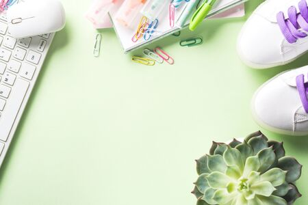 Pastel mint green back to school flat lay with blank white page, stationery, keyboard, succulent, sneakers. Workspace. Blogging concept