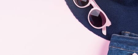 Pink fashion flat lay with girls clothes, sun glasses. Copy space