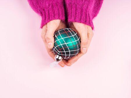 Die Hand der Frau in einem gemütlichen Pullover, der eine weihnachtliche grüne und rote Ornamentkugel auf rosafarbenem Hintergrund hält. Festliches Konzept